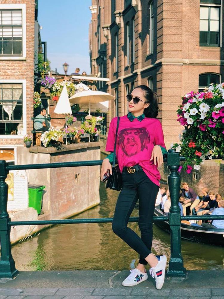 Hương Giang diện chiếc áo gam màu xanh cùng áo khoác màu hồng và phụ kiện thời thượng.
