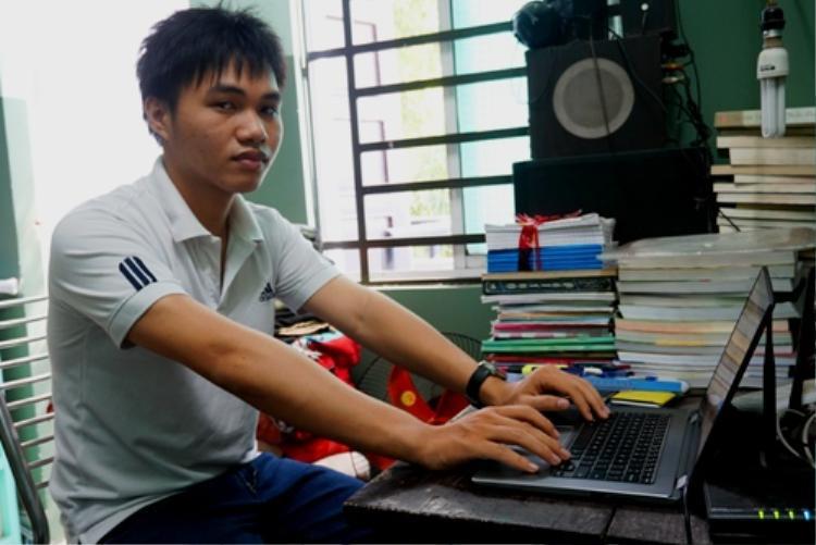 Phạm Phú Phong ngồi bên chiếc laptop trong góc học tập. Ảnh:Thạch Thảo.