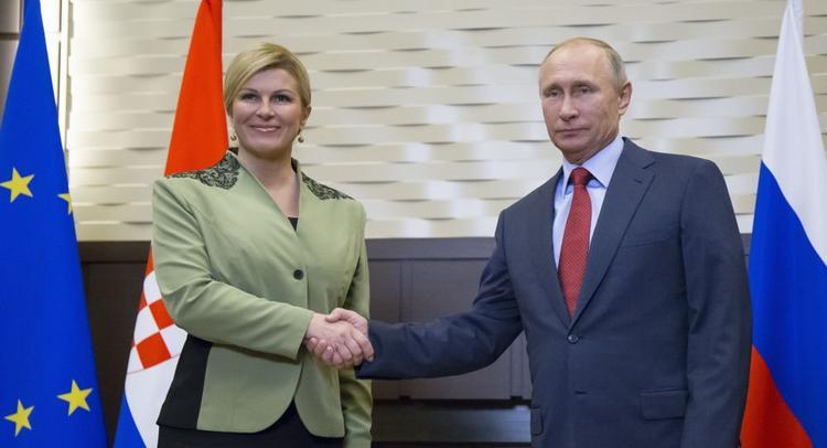 Trong cuộc gặp gỡ thượng đỉnh với người đồng cấp Putin, nữ tổng thống diện bộ suit màu xanh quân đội với họa tiết được đính trên cầu vai, bộ suit được nhiều người khen ngời.