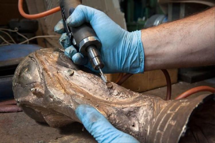 Sau khi thân cúp được lấy ra khỏi khuôn, khối kim loại đồng thau này được chau truốt lại để xử lý các phần kim loại thừa.