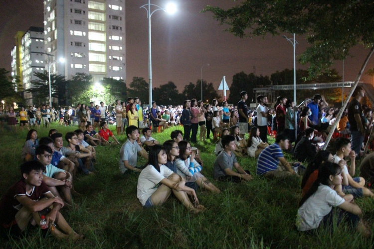 Không khí đông đúc, một số bạn sinh viên đến sau nguyện ngồi ở bãi cỏ để theo dõi