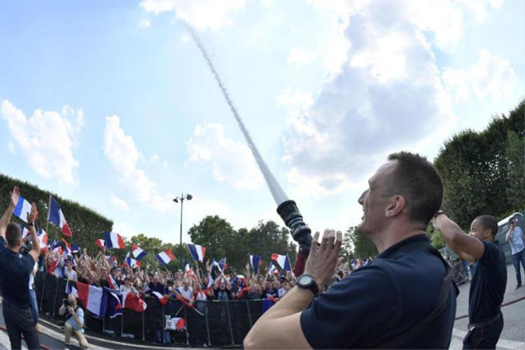 Dùng vòi cứu hỏa phun nước lên trời để ăn mừng. Ảnh: Mega Agency.