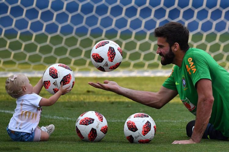 Thủ môn Allison của Brazil chơi với cô con gái Helena trong buổi tập trước trận gặp Bỉ.