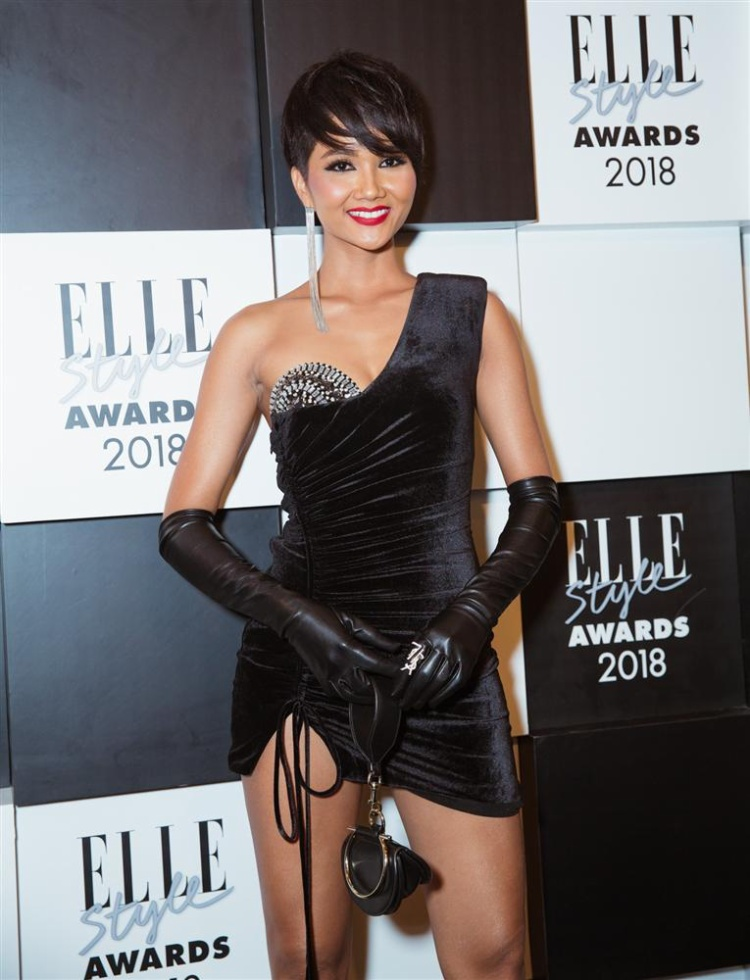 """Lần gần đây nhất, trên thảm đỏ Elle Style Awards 2018, thay vì sắc trắng an toàn quen thuộc, HHHV Việt Nam 2017 có cú """"lột xác"""" khiến người hâm mộ choáng váng.Chân dài diện thiết kế lệch vai chất liệu nhung của NTK Lưu Ngọc Kim Khanh. Đây là bộ cánh có kiểu dáng ngắn nhất từ trước đến nay mà H'Hen Niê từng diện khi tham dự sự kiện. Chiếc váy có sự đột phá nhưng lại không nhận được đánh giá cao từ giới điệu mộ bởi cách kết hợp găng tay da không phù hợp."""
