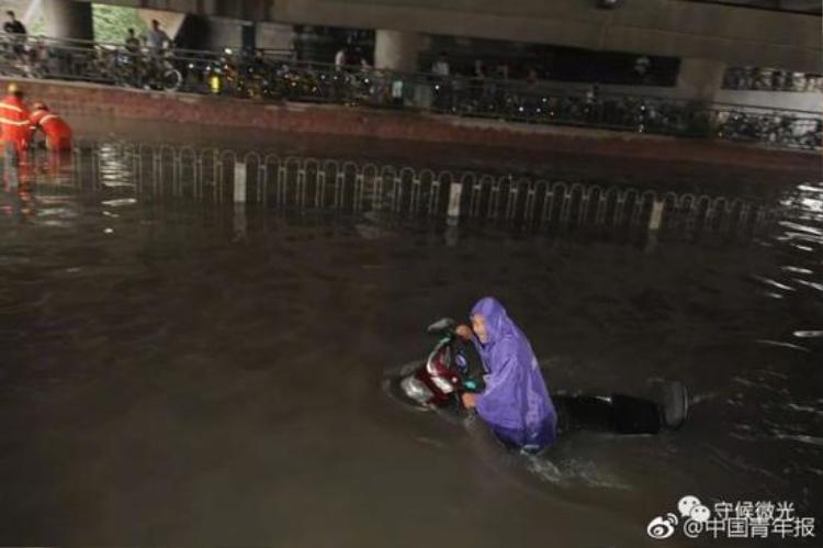 Mưa lụt tới ngang hông, ngập cả xe máy khiến người dân không thể di chuyển.