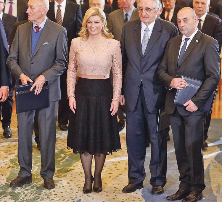 Bà Kolinda vô cùng duyên dáng khi đứng cùng hàng ngũ các nhà lãnh đạo với chiếc váy ren phối màu khéo léo giữa tông hồng bụi và sắc đen tuyền.