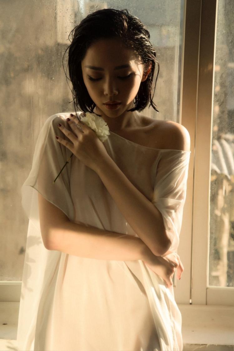 """Khác với những trang phục táo bạo khoe đường cong triệt để trước đây, lần này giọng ca """"Em không là duy nhất"""" chỉ trưng diện những chiếc đàm trắng đơn giản với chất liệu mềm rũ làm tăng vẻ dịu dàng, nữ tính nhưng vẫn toát lên sự quyến rũ bí ẩn bởi thần thái u sầu."""