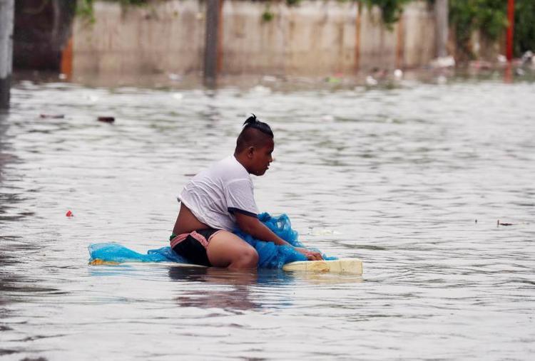 Một người đàn ông ngồi trên chiếc bè thô sơ, cố gắng di chuyển theo một con đường bị ngập lụt. Ảnh: Reuters