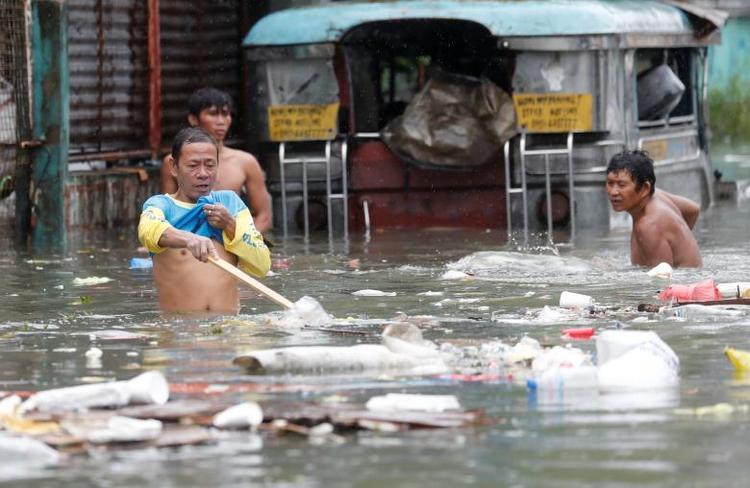 Cư dânthành phố Quezon đang thu gom rác thải nổi lềnh bềnh trên mặt nước. Ảnh: Reuters