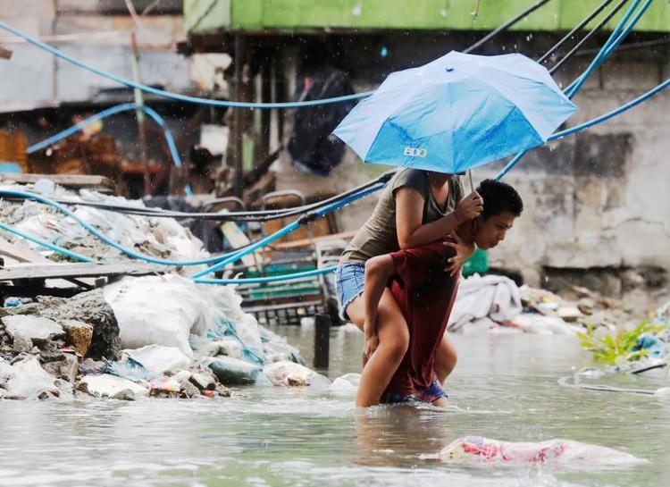 Mưa lớn khiến nhiều trường học phải tạm ngừng đóng cửa. Trong ảnh là một người đàn ông cõng một người phụ nữ men theo con đường ngập lụt để đến nơi an toàn. Ảnh: Reuters