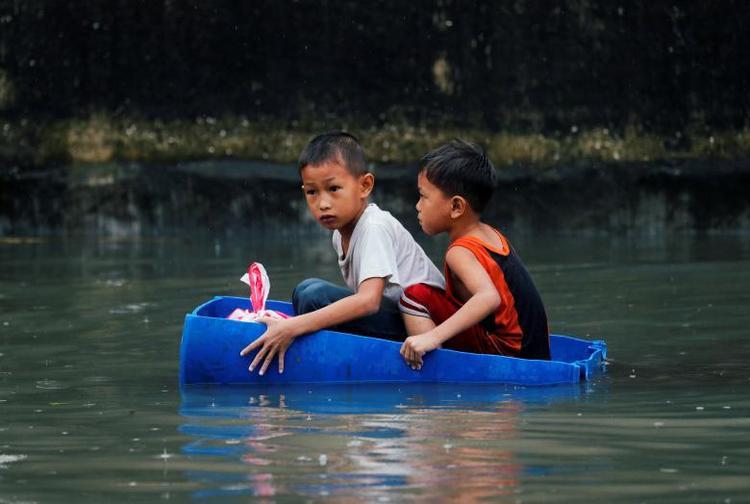 Những đứa trẻ trôi nổi trong một chiếc thùng nhựa trên dòng nước lũ. Ảnh: Reuters