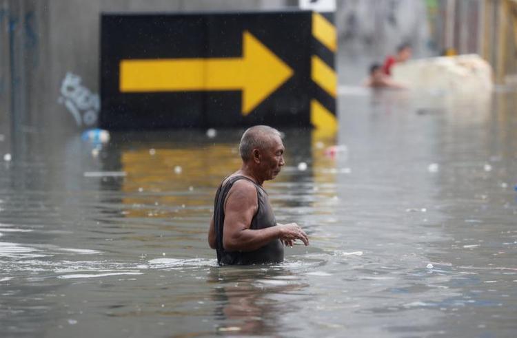 Ngày 17/7, đường phố Manila,Philippines bị ngập lụt vì mưa lớn kéo dài trong nhiều ngày kết hợp ảnh hưởng do bão Sơn Tinh. Ảnh trên là cảnh ngập úng ở thành phố Quezon thuộc vùng đô thị Manila. Ảnh: Reuters