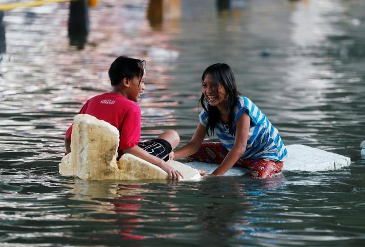 Những đứa trẻ khác chơi đùa trên con đường bị ngập lụt. Ảnh: Reuters