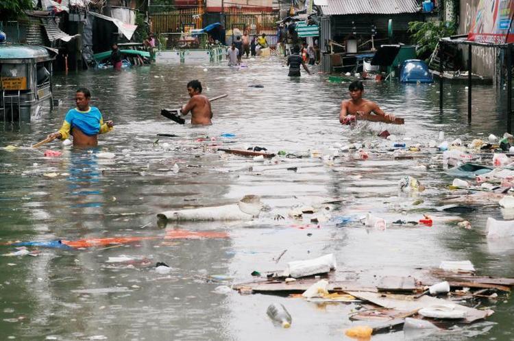 Mưa gây ngập úng trên diện rộng khiến rác thải trôi, nổi lềnh bềnh trên dòng nước tại các khu dân cư có thu nhập thấp. Ảnh: Reuters