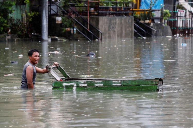 Mực nước dâng cao tới thắt lưng của một người đàn ông. Ảnh: Reuters