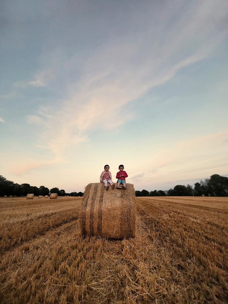 """Giải ba Trẻ em - """"Twins"""": Tôi chụp hình này vào tháng 8 năm 2017. Tôi không thể cưỡng lại được việc chụp hình khi bầu trời và cánh đồng trông thật tuyệt và những em bé trên đống rơm khiến mọi thứ đặc biệt thêm. Chụp bằng iPhone 7 Plus. Xử lý với VSCO (Savadmon Avalachamveettil)"""