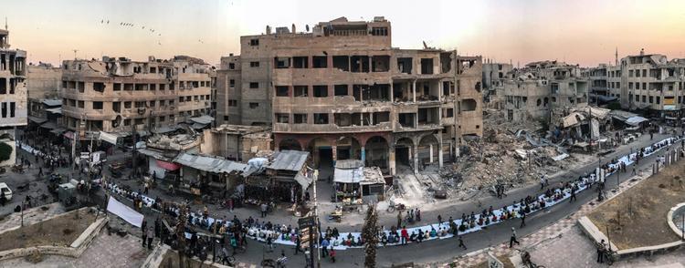"""Giải nhất Tin tức và Sự kiện - """"ftar Amongst the Ruins"""": Người Syria ngồi cùng nhau trên một chiếc bàn dài 1.200 mét để ăn tối vào dịp lễ Ramadan. Chụp bằng iPhone 7. (Mohammed Badra)"""