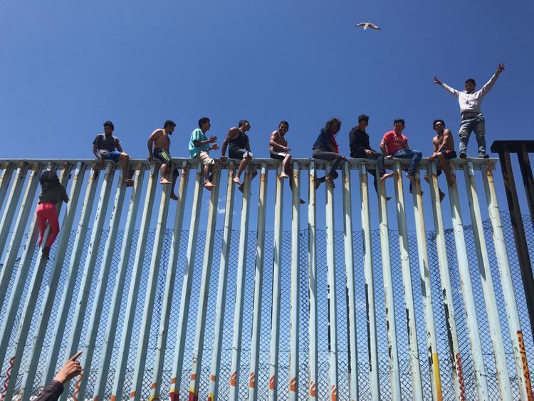 """Giải ba Tin tức và Sự kiện - """"Refugee Caravan"""": Một số người đứng trên đường chia cắt biên giới giữa Mỹ và Mexico. Chụp bằng iPhone 6s. (Verónica G. Cárdenas)"""