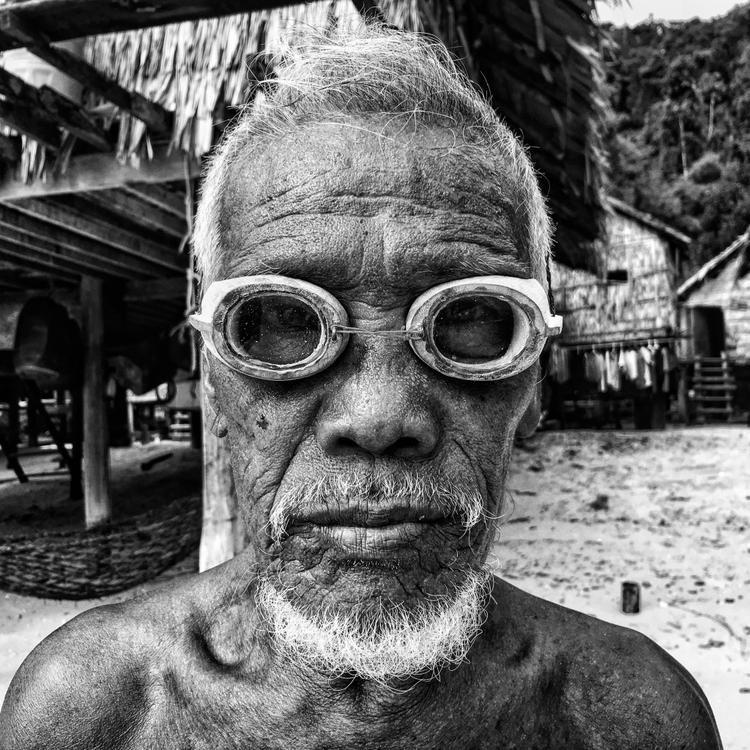 """Giải nhất Chân dung - """"Salamah"""": Salamah đeo một chiếc kính lặn khắc gỗ trên bãi biểu ở Au Bon Yai. Chụp bằng iPhone 6s. (Scott Woodward)"""