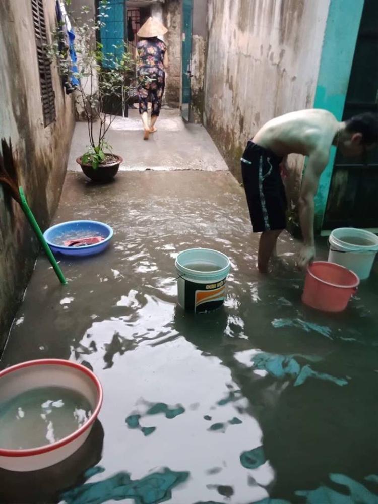 Người dân ở Hoàng Mai phải dùng chậu múc nước ra khỏi nhà.