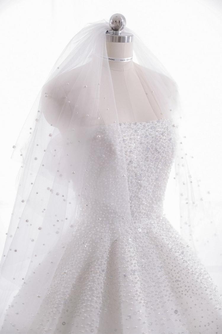 Theo tiết lộ, NTK Chung Thanh Phong đã cẩn thận thực hiện váy cưới cho Á hậu Tú Anh trong vòng 1 tháng. 20.000 viên pha lê và đá Swarovski được đính kết trên thân áo và khăn voan đội đầu cực kì tỉ mỉ.