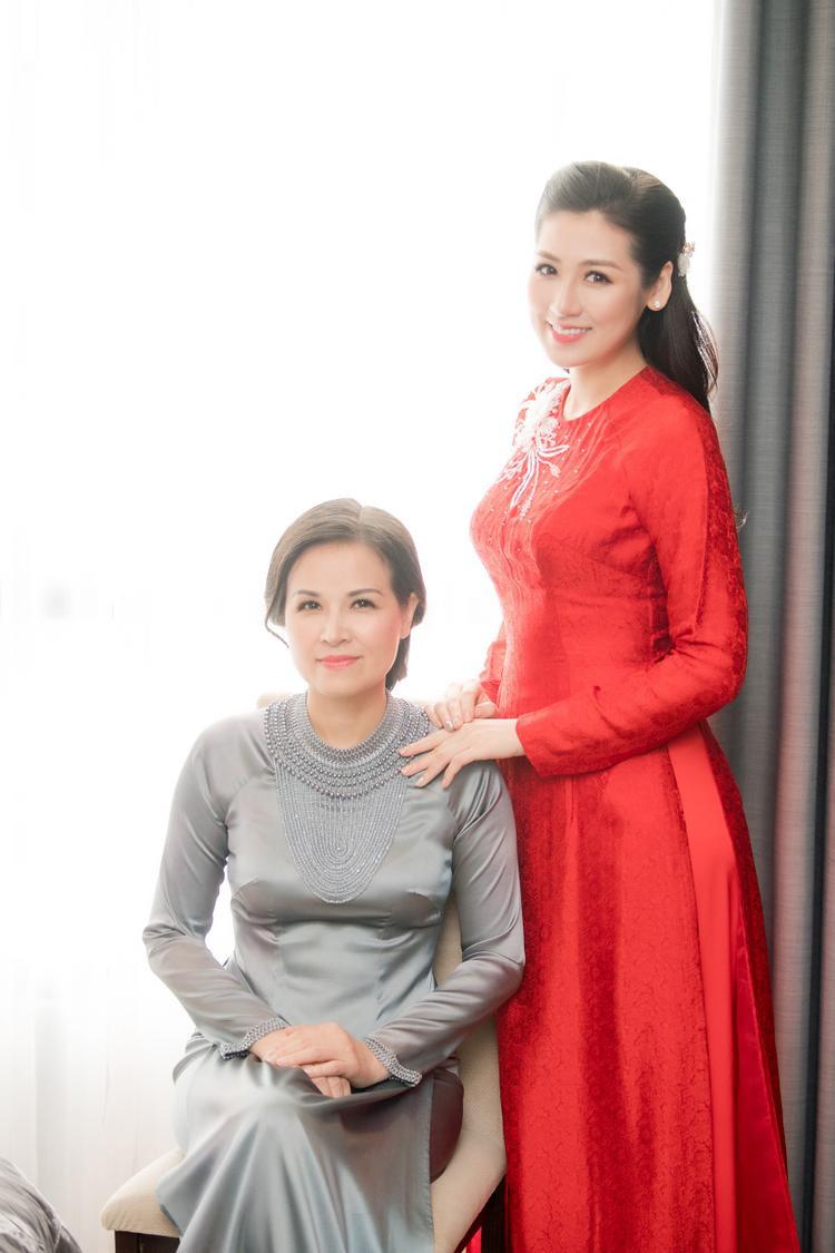 Trước đó trong lễ vu quy diễn ra tại tư gia, mỹ nhân sinh năm 1993 đẹp dịu dàng trong tà áo dài đỏ nổi bật được thêu hoa văn tinh tế. Cô dâu trang điểm nhẹ nhàng, tóc bới nhẹ và rạng rỡ tạo dáng cùng mẹ.