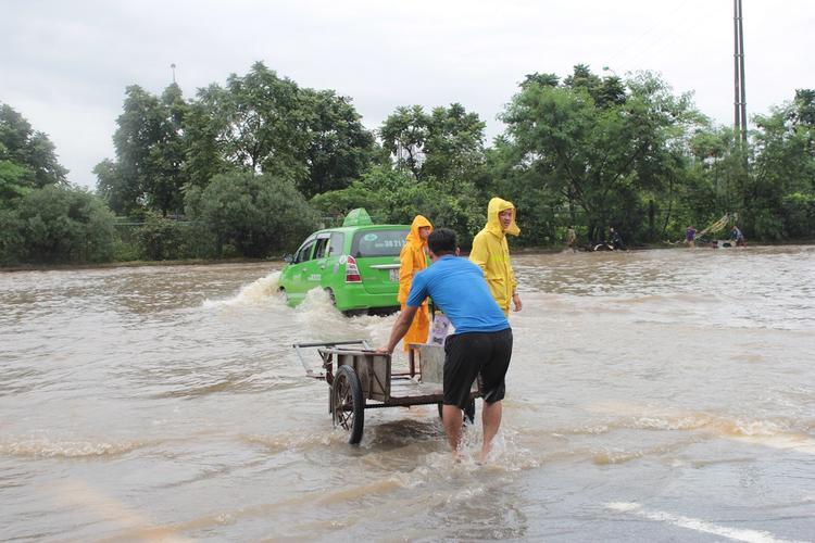 """Nhân cơ hội này, nhiều người có xe ba gác """"tranh thủ"""" làm dịch vụ chở khách trong mưa lũ."""