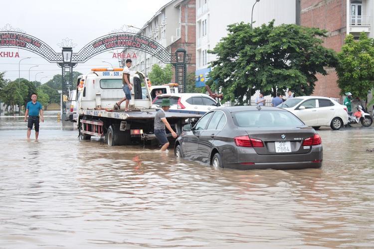 Một chiếc ô tô bị chết máy được đưa ra khỏi đoạn đường ngập lụt.
