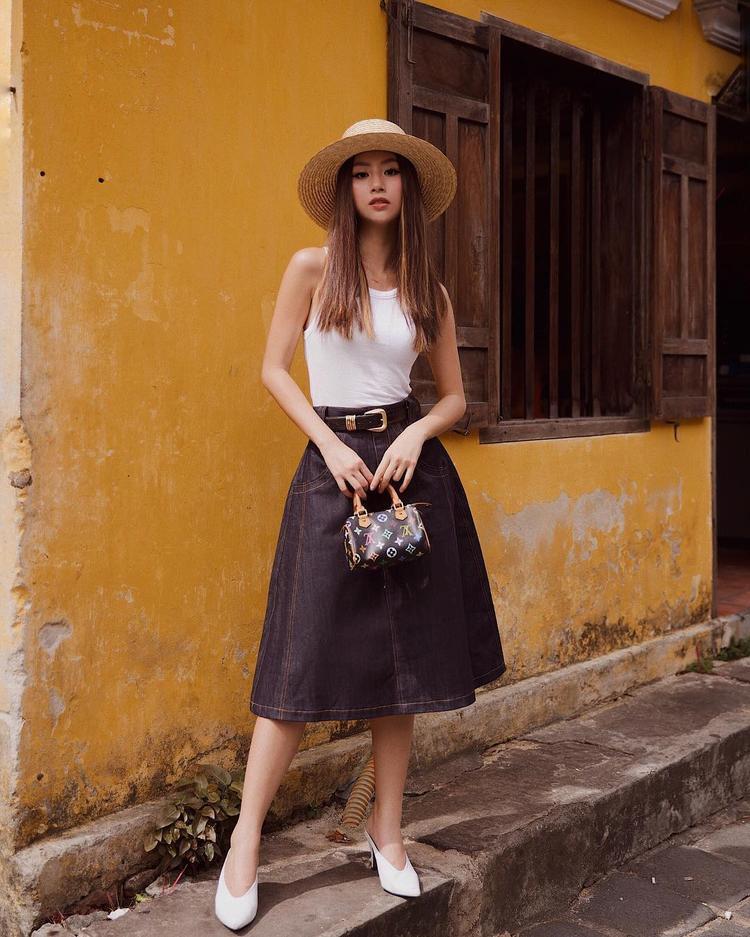 Xuống phố tại Hội An, Quỳnh Anh Shyn nhanh nhạy trưng dụng set đồ đơn giản với váy xòe và áo ba lỗ. Cô nàng không quên phối cùng cao gót cổ chữ V và túi cói để hoàn thiện tổng thể.