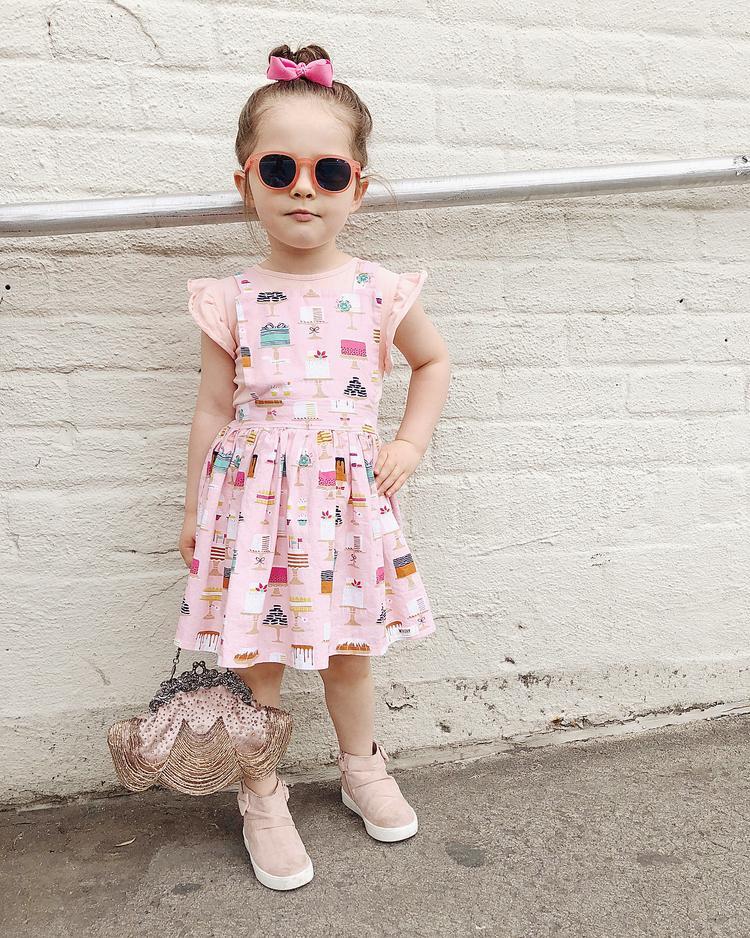 Một bé gái đáng yêu trong chiếc váy hồng họa tiết vui mắt lập tức trở lên chất ngất với mắt kính đen viền cam và túi xách kiểu dáng độc đáo.