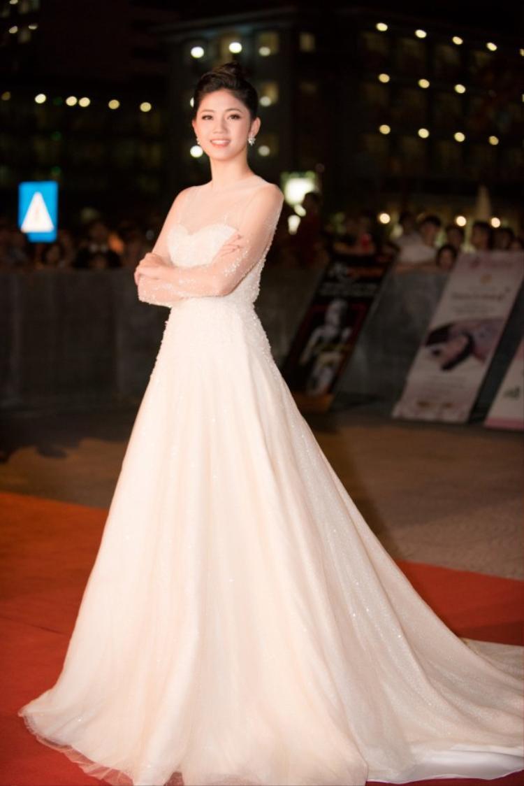 Á hậu Tú Anh hóa công chúa kiều diễm với chiếc váy xòe dài tha thướt. Sắc trắng nhẹ nhàng cùng cách kết hợp chất liệu xuyên thấu ngay tay đem lại cho cô vẻ nữ tính, nổi bật mà không hề phô phang.