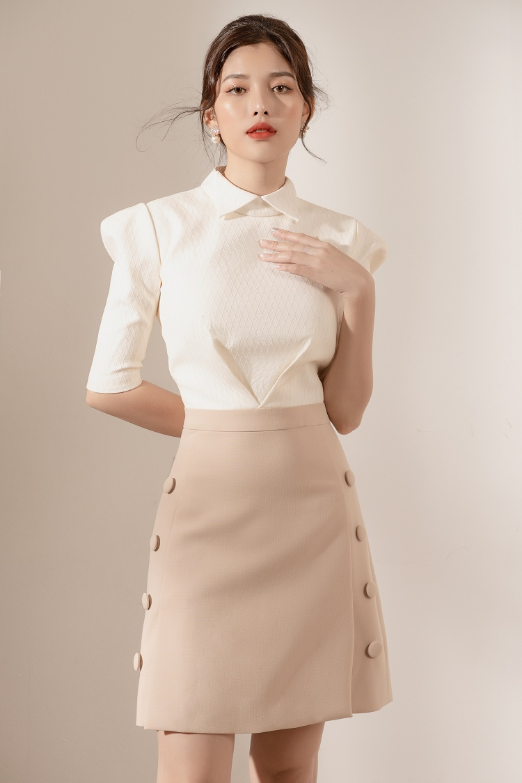Váy chữ A với các hàng khuyên nút song song màu kem kết hợp với áo trắng dài tay kiểu cách.