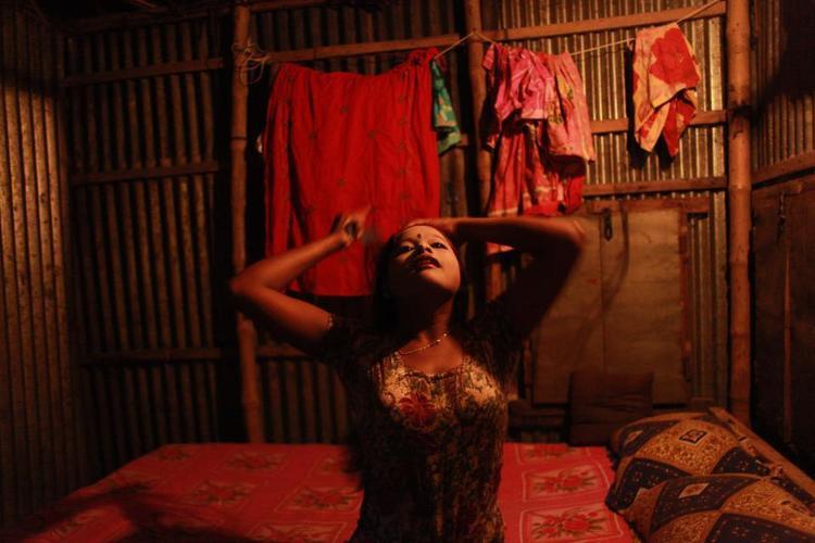 Các cô gái nhỏ từ 11 tuổi bị buộc phải làm việc trong các nhà thổ ở Bangladesh. Đây là hình ảnh cô bé vị thành niên Sonia đang trang điểm sao cho già hơn để phục vụ khách hàng của mình.