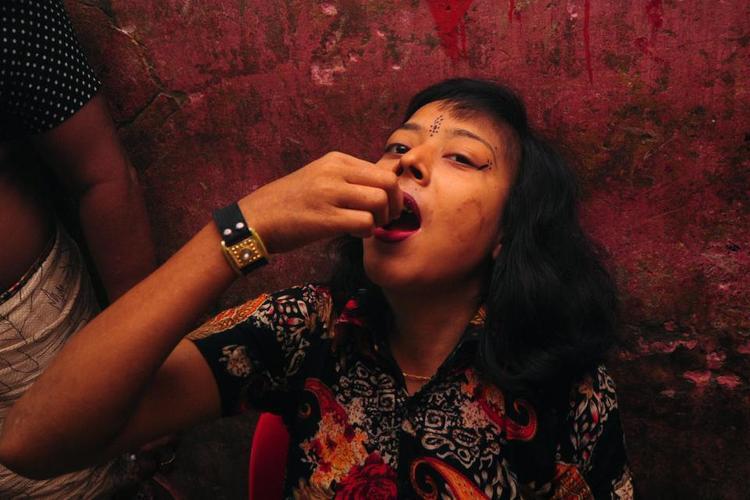 Gái mại dâm trẻ em ở Bangladesh được cho ăn Oradexon, một loại steroid bò, để khiến cơ thể họ phát triển nhanh hơn. Cô gái Rokeya trong ảnh đang uống thuốc trong một nhà thổ ở Faridpur, cách thủ đô Dhaka 60 dặm.