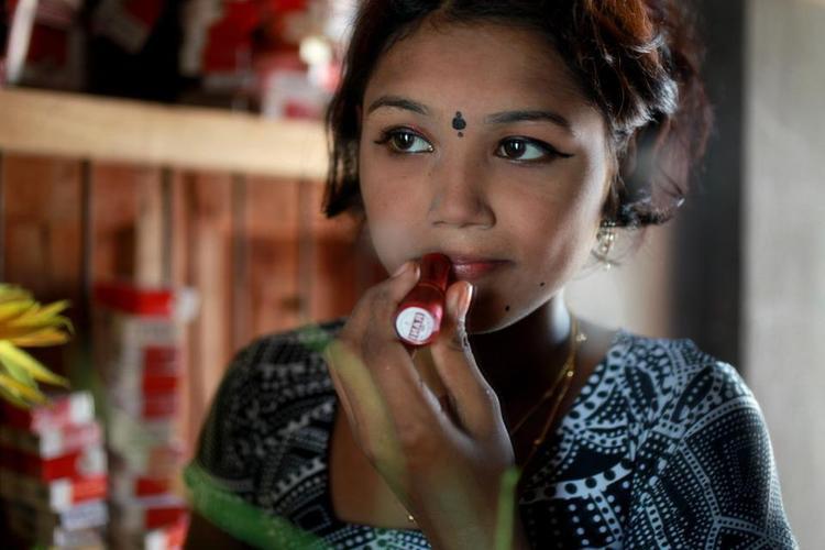 """Đàn ông Bangladesh trưởng thành trả khoảng 1,75 bảng Anh (khoảng hơn 53.000 VND) cho 10 phút """"gần gũi"""" với các cô gái vị thành niên như Bristi, người đang trang điểm tại một nhà chứa ở Daulatdia. Cô là một trong 2.000 gái mại dâm làm việc ở đó."""