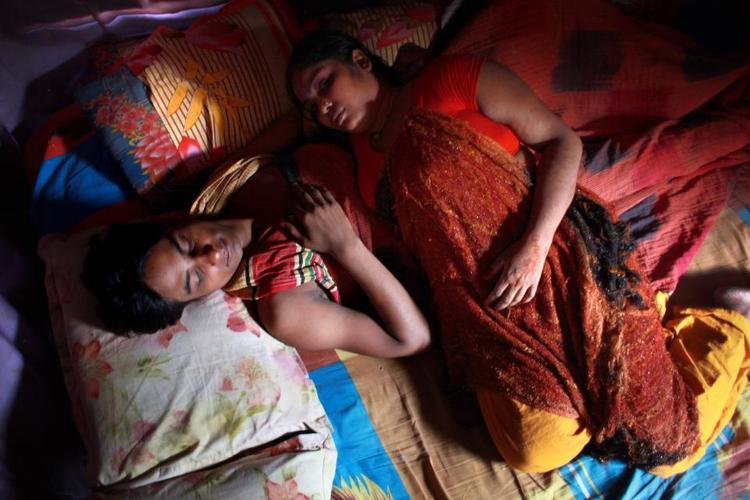 """Misumi, không rõ tuổi tác, đang nằm cùng một khách hàng thường xuyên trong nhà chứa lớn nhất nước ở Daulatdia, Bangladesh. Những người đàn ông trở lại thường xuyên được gọi là """"bạn trai"""" và ít sử dụng bao cao su hơn."""
