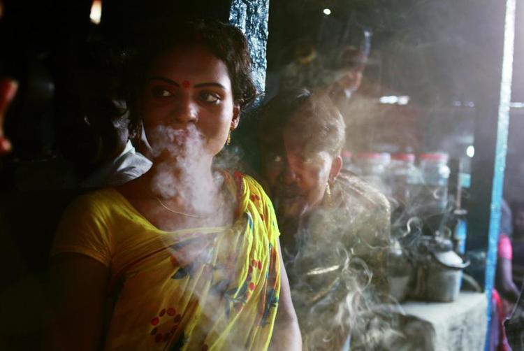 Một công nhân tình dục tuổi vị thành niên đang hút thuốc khi chờ đợi khách.