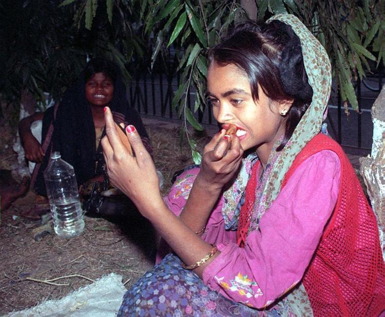 Reshma, mới 14 tuổi khi bức ảnh này được chụp, là một trong số 20.000 gái mại dâm đường phố làm việc tại thủ đô Dhaka của Bangladesh. Cô ấy đang trang điểm trong khi một người bạn đang nhìn.