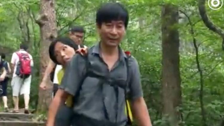 Anh Wang địu vợ đi xuống đỉnh Hoàng Sơn (ảnh cắt từ clip).