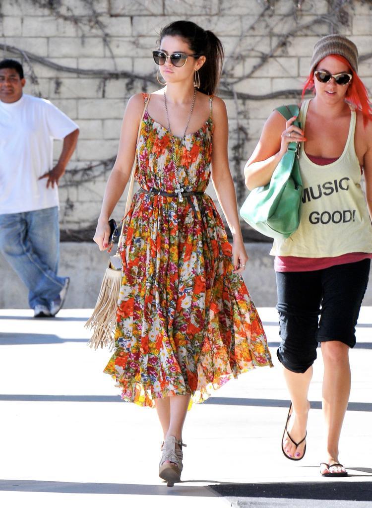 Váy hoa hai dây xòe kết hợp với túi xách tua rua và chiếc belt nhỏ thắt ngang lưng.