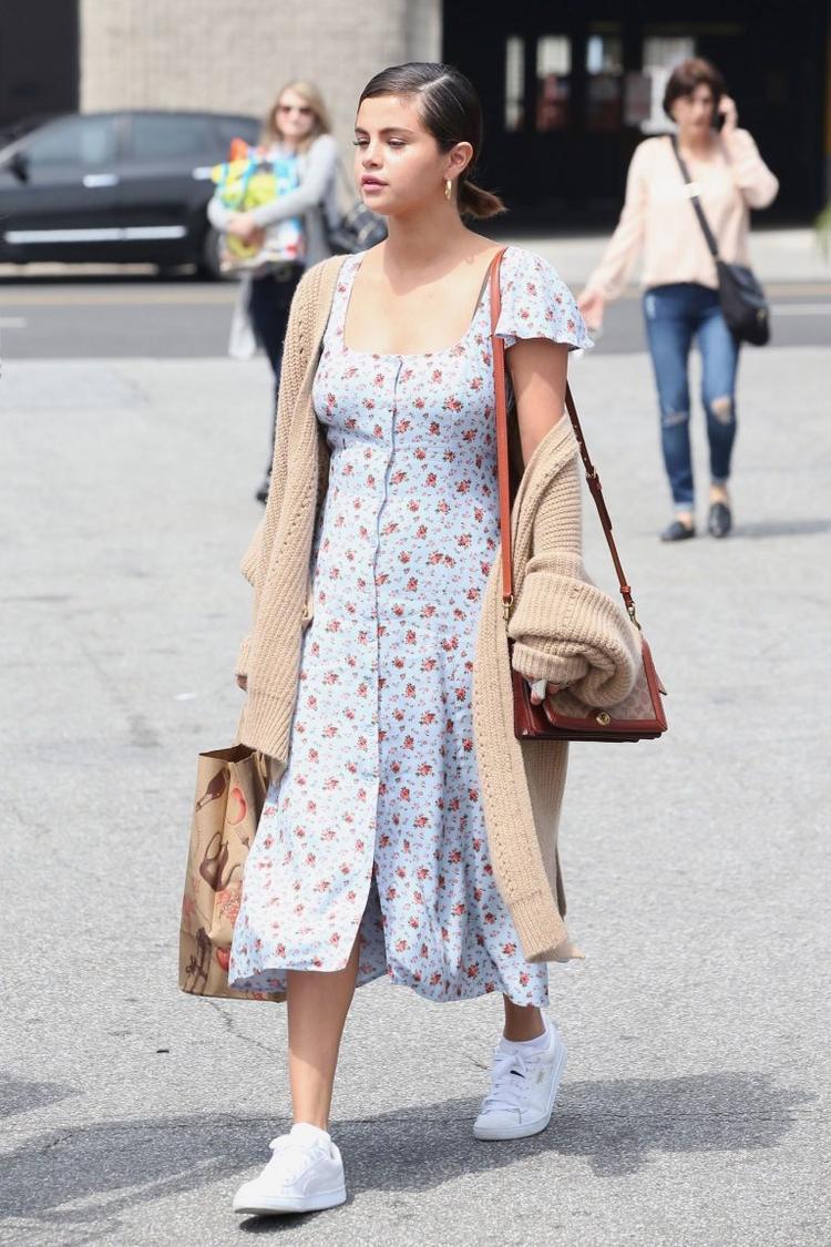 Sự kết hợp của chiếc cardigan len móc màu nâu cùng túi da và khuyên tai vòng vàng giúp tăng thêm tính retro cho chiếc váy đồng cỏ cổ vuông