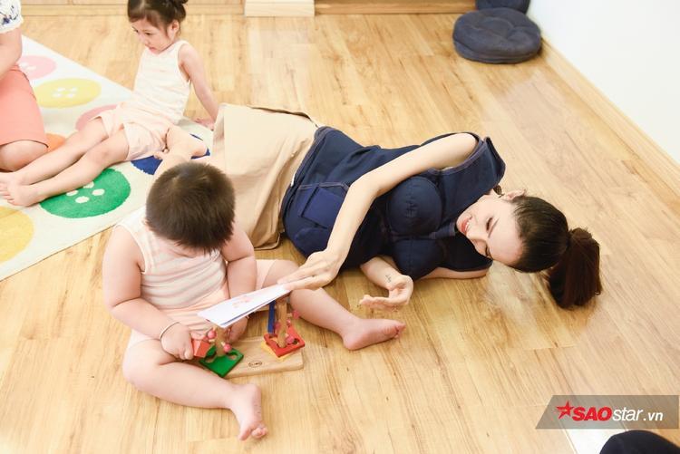 Có ai đáng yêu như Hương Giang, nằm lăn ra sàn nhà chơi đùa cùng trẻ.