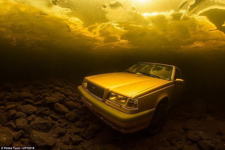 """Pekka Tuuri, đến từ Phần Lan, chụp bức ảnh này dưới đáy hồ Saimaa, Phần Lan. """"Chiếc xe này bị chìm trong băng. Để có thể chụp được nó, tôi phải đi xe trong 4 giờ đồng hồ, sau đó tiến hành khoan một lỗ rộng 20 m. Quả thực tôi khá may mắn"""", ông tiết lộ."""