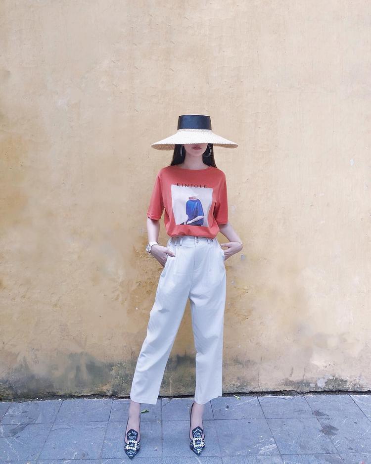 """Mũ cói che nửa mặt cùng giày cao gót sang chảnh là hai món phụ kiện """"ăn tiền"""" giúp Jolie Nguyễn """"tỏa sáng"""" trong set đồ đơn giản."""