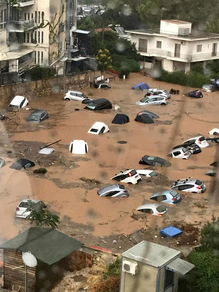 Hàng trăm chiếc xe ô tô bị nhấn chìm trong vũng nước bùn đục ngầu sau khi mưa lớn xảy ra ở Maroussi, ngoại ô Athens.