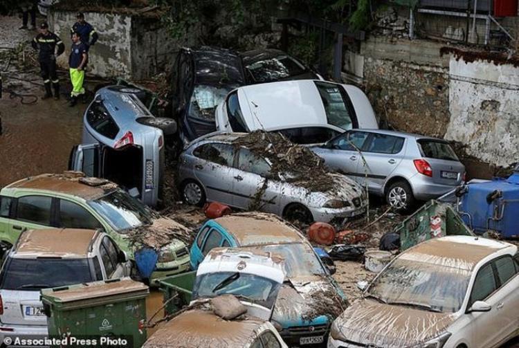 Những chiếc xe ô tô nằm ngổn ngang trên đường phố sau trận lũ lụt trông giống như đống phế liệu.