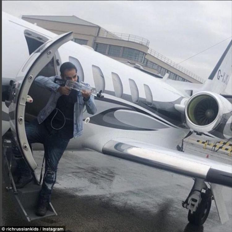 Một anh chàng tạp dáng với một chai rượu khi đang bước ra khỏi một máy bay tư nhân.