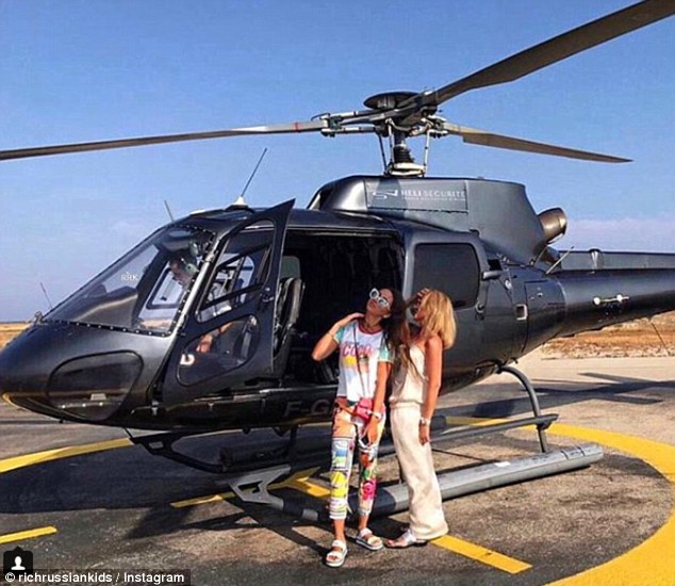 Hai cô nàng tạo dáng trước một chiếc máy bay trực thăng.