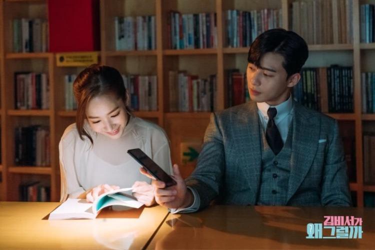Ra dáng đàn ông, anh soi đèn cho thư ký Kim đọc sách.