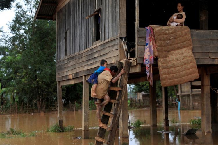 Hai cha con trở về nhà sau cơn lũ. Hiện, người dân Lào vẫn cần lương thực, thuốc men để duy trì cuộc sống tạm thời. Ảnh: Reuter.
